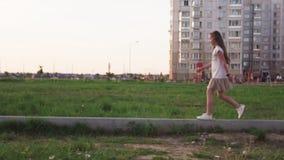 Cute little girl walking on concrete log on city lawn stock video