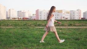Cute little girl walking on grass on urban wasteland stock video footage