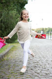 Cute little girl walking with the pink shopping bags Stock Photos