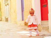 Cute little girl walking on the street of Malta Stock Photo