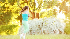 Cute little girl walking under tree in the park at sunshine summer day. Happy child in the sportwear, in green leggings, t-shirt and with sportive shoes. Happy stock video
