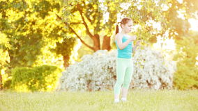 Cute little girl walking under tree in the park at sunshine summer day. Happy child in the sportwear, in green leggings, t-shirt and with sportive shoes. Happy stock footage