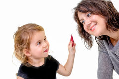 Cute little girl wants to apply her mothers makeup Stock Photos
