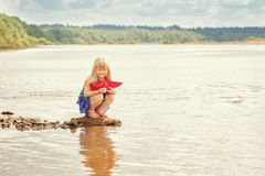 Cute little girl wants to run paper boat in lake Royalty Free Stock Images