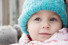 A cute little girl in a warm blue hat close-up, Royalty Free Stock Photos