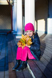 Cute little girl in warm clothes with yellow leaves sitting on t Royalty Free Stock Images