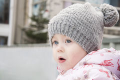 A cute little girl in a warm hat close-up, Stock Photo