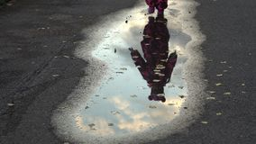 Pretty baby girl in a warm pink overalls running through puddles stock video
