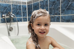 Cute little girl washes her hair. Clean kid after shower. Childr. En hygiene. Child taking bath. Little baby in a kitchen sink washing hair with shampoo and soap Royalty Free Stock Images