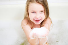 Cute little girl washing in bath. And playing with soap bubbles Royalty Free Stock Photo