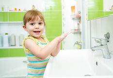 Cute little girl washing in bathroom Stock Photo