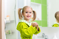 Cute little girl washing hands in bathroom Royalty Free Stock Image