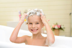 Cute little girl washing her hair. On the edge of delight. Pleasant smiling little girl sitting in the bath tube and washing her hair while feeling glad stock image