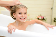 Cute little girl washing her hair. Full of delight. Pleasant little girl sitting in the bath tube and smiling while her mother washing her hair stock images