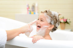 Cute little girl washing her hair. Joyful moment. Cute smiling little girl sitting in the bath tube and taking bath while having fun with her mother royalty free stock image