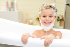 Cute little girl washing her hair. Lets play. Cheerful content little girl sitting in the bath tube and having fun while washing her hair stock photo