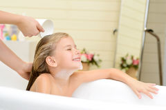 Cute little girl washing her hair. Like this moment. Pleasant cute little girl sitting in the bath tube and closing her eyes while her mother washing her hair stock photography