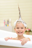 Cute little girl washing her hair. Like the process. Cute little girl sitting in the bath tube and washing her hair while having fun royalty free stock image
