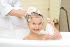 Cute little girl washing her hair. My favorite liquid. Pleasant smiling little girl sitting in the bath tube and holding bottle of shampoo while washing hair royalty free stock photography