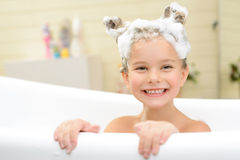 Cute little girl washing her hair. Play with me. Content cheerful little girl sitting in the bath tube and smiling while having fun stock photos