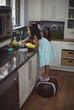 Cute little girl washing utensil in kitchen sink Stock Photos