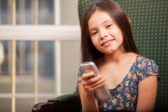 Cute little girl watching TV. Portrait of a pretty Hispanic little girl holding a TV remote and smiling Stock Photography
