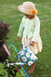 Cute little girl watering flowers in the garden. Cute little girl with watering can working in the garden Royalty Free Stock Photos