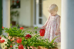 Cute little girl watering flowers Stock Image
