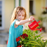 Cute little girl watering flowers Stock Photos
