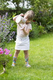 Cute little girl watering flowers in garden Stock Images