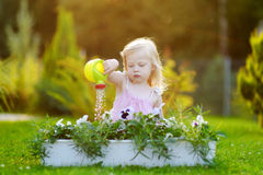 Cute little girl watering flowers in the garden Stock Photography