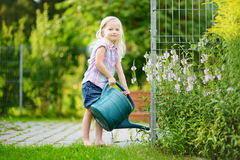 Cute little girl watering flowers in the garden Royalty Free Stock Images