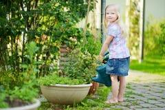 Cute little girl watering flowers in the garden Stock Photo