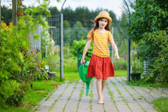 Cute little girl watering flowers in the garden Royalty Free Stock Photo