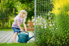 Cute little girl watering flowers in the garden Royalty Free Stock Photos