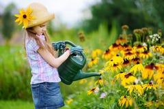 Cute little girl watering flowers in the garden Stock Photos