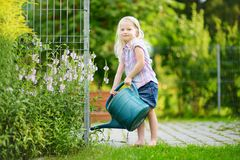 Cute little girl watering flowers in the garden Stock Images