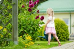 Cute little girl watering flowers in the garden at summer day. Child using garden hose on sunny day Royalty Free Stock Photography