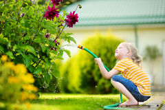 Cute little girl watering flowers in the garden at summer day. Stock Images