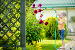 Cute little girl watering flowers in the garden at summer day. Royalty Free Stock Photo