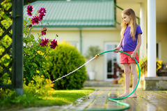 Cute little girl watering flowers in the garden at summer day. Stock Photos