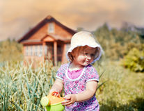 Cute little girl watering garden