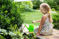 Cute little girl watering plants in the garden Royalty Free Stock Photos