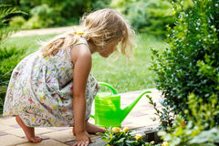 Cute little girl watering plants in the garden. stock photos