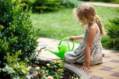 Cute little girl watering plants in the garden. Royalty Free Stock Image