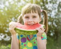 Cute little girl with watermelon. On the background of nature Royalty Free Stock Images