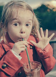 Cute little girl waving as drinking hot chocolate on straw Stock Images