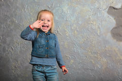 Cute little girl waving her hand and posing to camera. Cute toddler girl posing joyfully to camera. Waving her hand laughing. Vintage background. Happy childhood Royalty Free Stock Image