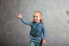 Cute little girl waving her hand and posing to camera. Cute toddler girl posing joyfully to camera. Waving hand. Vintage background. Happy childhood, beautiful Royalty Free Stock Photo
