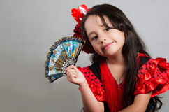 Cute little girl wearing beautiful red and black dress with matching head band, posing for camera using chinese hand fan. Studio background Royalty Free Stock Image